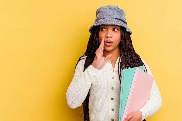 Young african american student woman isolated on yellow wall is saying a secret hot braking news and looking aside