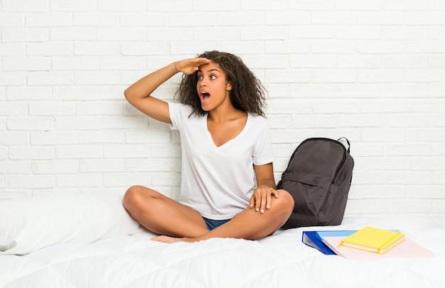 額に手を置いて遠くを見ているベッドの上の若いアフリカ系アメリカ人学生の女性。