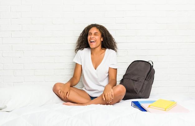 ベッドの上の若いアフリカ系アメリカ人学生女性はリラックスして幸せな笑い、歯を見せて首を伸ばした。