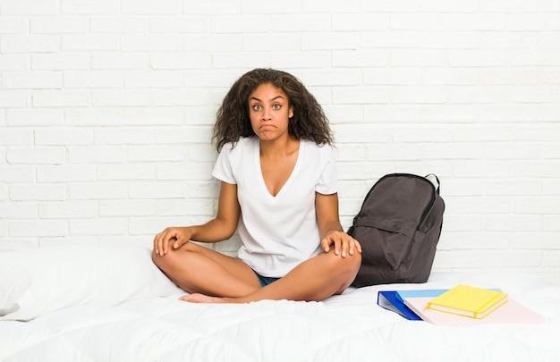 ベッドの上の若いアフリカ系アメリカ人学生の女性は肩をすくめ、開いた目は混乱しています。