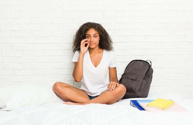 비밀을 유지하는 입술에 손가락으로 침대에 젊은 아프리카 계 미국인 학생 여자.