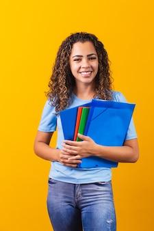 黄色の背景のスタジオの肖像画に分離された本を保持しているカジュアルな服を着た若いアフリカ系アメリカ人の10代の学生。高校、大学、大学のコンセプトでの教育。コピースペースをモックアップします。垂直