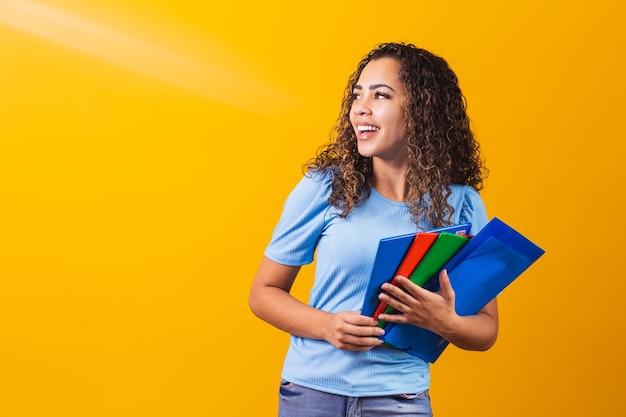 黄色の背景のスタジオの肖像画に分離された本を保持しているカジュアルな服を着た若いアフリカ系アメリカ人の10代の学生。高校、大学、大学のコンセプトでの教育。コピースペースのモックアップ