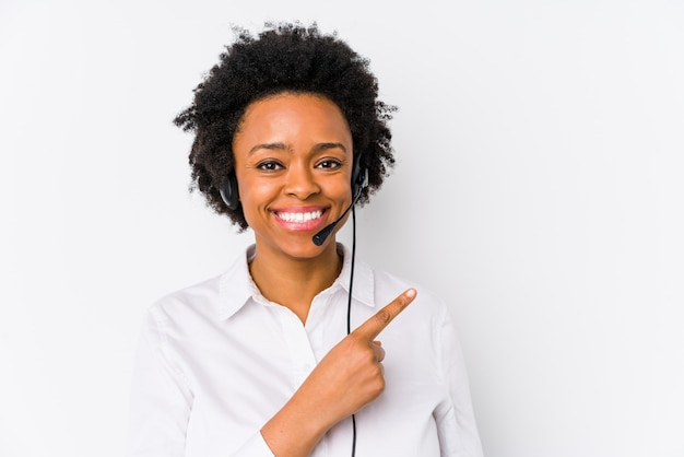 Young african american telemarketer woman isolated smiling and pointing aside, showing something at blank space.
