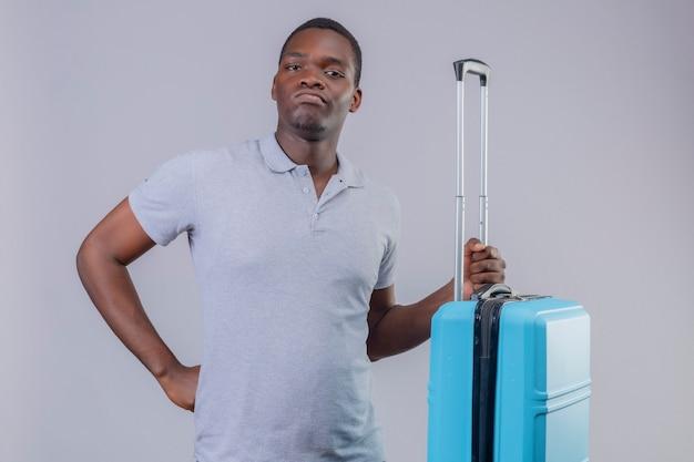 Uomo giovane viaggiatore afroamericano in camicia di polo grigia che tiene la valigia blu scontenta e accigliata