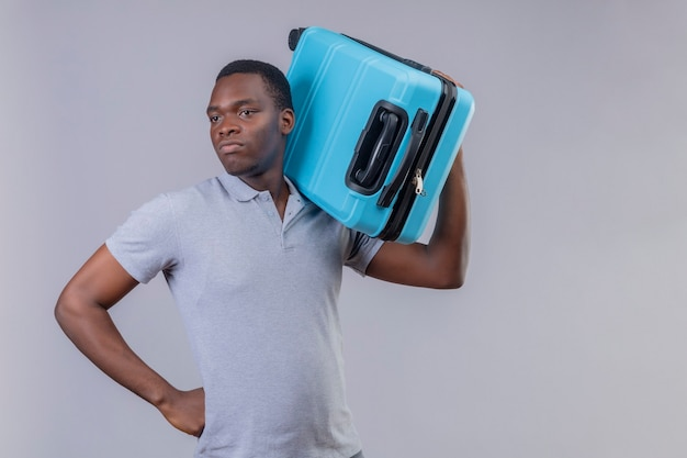 Young african american traveler man in grey polo shirt holding blue suitcase looking aside displeased and frowning