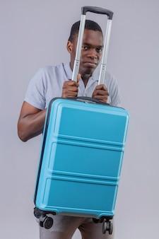 Uomo del giovane viaggiatore afroamericano in camicia di polo grigia che tiene la valigia blu che osserva macchina fotografica di ta dispiaciuto che si nasconde dietro la valigia