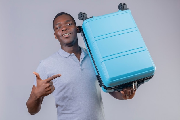 Uomo del giovane viaggiatore afroamericano in camicia di polo grigia che tiene la valigia blu che indica con il dito che sembra positivo e felice