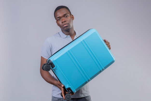Young african american traveler man in grey polo shirt holding blue suitcase  with unhappy face
