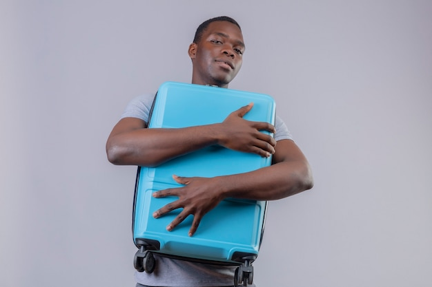 Young african american traveler man in grey polo shirt hugging his blue suitcase with confident smile on face