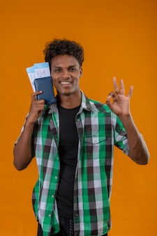 オレンジ色の背景の上に立ってokの標識をやってカメラを見て明るく陽気で幸せな笑顔の航空券を保持している若いアフリカ系アメリカ人旅行者男