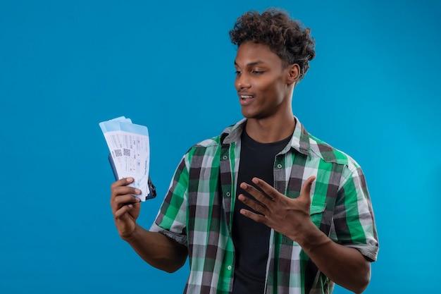 青い背景の上に立って終了した陽気な肯定的で幸せな航空券を見て航空券を保持している若いアフリカ系アメリカ人旅行者の男性終了立った