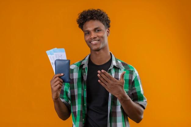 オレンジ色の背景の上に立っているカメラを見て彼の手の腕を明るく陽気で幸せな提示笑みを浮かべて航空券を保持している若いアフリカ系アメリカ人旅行者男