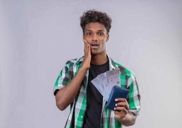 Молодой афро-американский путешественник мужчина, держащий авиабилеты, удивлен и поражен, глядя в камеру, покрывающую моль, с рукой, стоящей на белом фоне