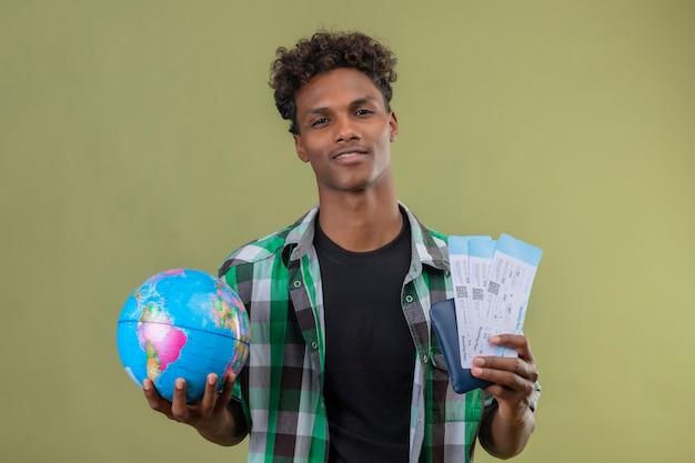 녹색 배경 위에 서 웃 고 카메라를보고 글로브와 항공 티켓을 들고 젊은 아프리카 계 미국인 여행자 남자