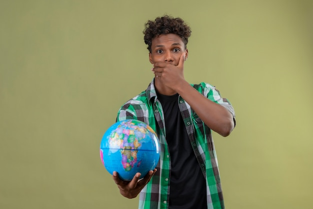 Young african american traveler man holding globe looking at camera shocked covering mouth with hand standing over green background