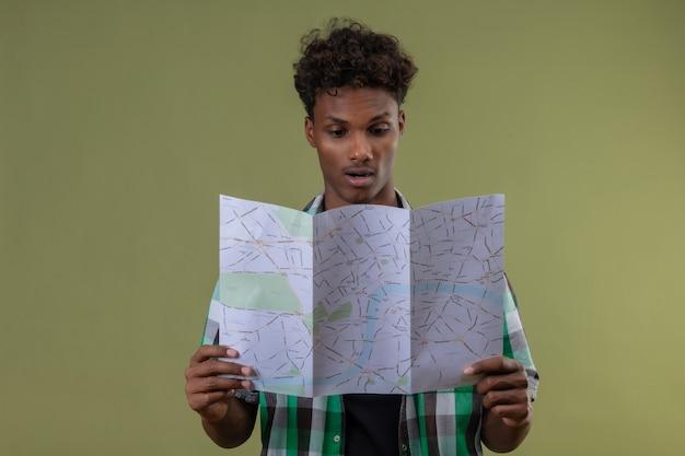 緑の背景の上に立って驚いてそれを見て地図を保持している若いアフリカ系アメリカ人旅行者男