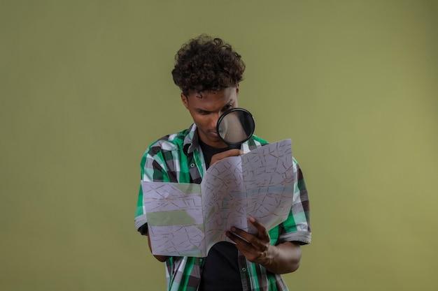 緑の背景の上に立っている虫眼鏡を通してそれを見て地図を保持している若いアフリカ系アメリカ人旅行者男