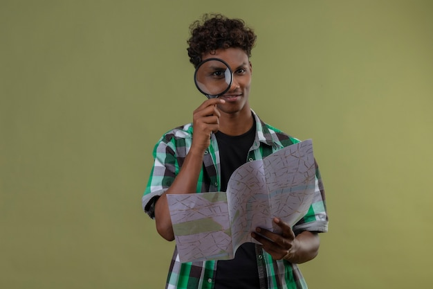 Young african american traveler man holding map looking at camera through magnifying glass smiling standing over green background