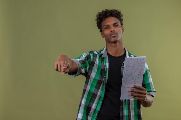 緑の背景の上に立っている顔に自信を持ってans深刻な表情でカメラを見てカメラを指しているマップを保持している若いアフリカ系アメリカ人旅行者男