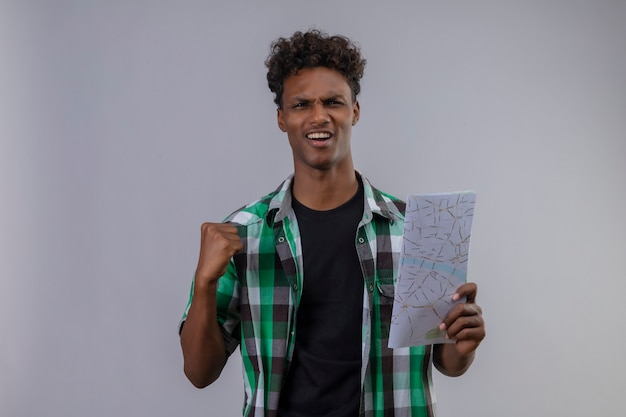 拳を上げるマップを保持している若いアフリカ系アメリカ人旅行者が終了し、白い背景の上に立って彼の成功を喜んで幸せな拳を上げる