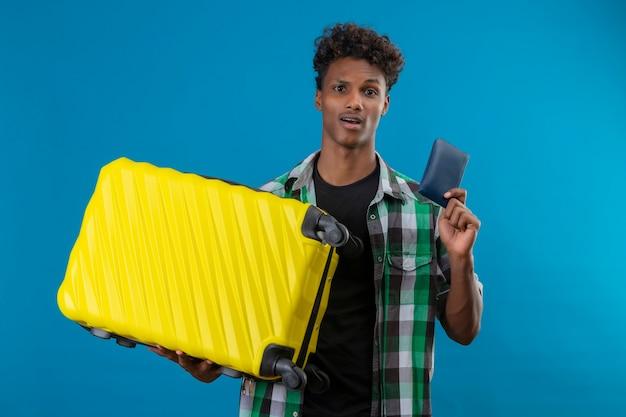 Молодой афро-американский путешественник мужчина держит чемодан и бумажник, глядя в камеру, смущенный и удивленный, стоя на синем фоне