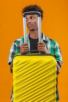 オレンジ色の背景の上に立っている答えを持っている混乱してよそ見スーツケースを持って若いアフリカ系アメリカ人旅行者男