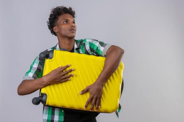 白い背景の上に立っている顔に恐怖の表情でよそ見スーツケースを持って若いアフリカ系アメリカ人旅行者男