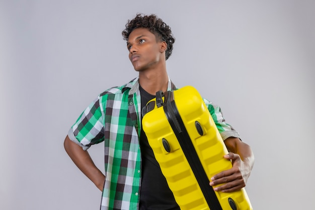 Молодой афро-американский путешественник мужчина держит чемодан, глядя в сторону с задумчивым выражением лица, думая