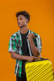 Young african american traveler man holding suitcase looking aside with serious confident expression on face