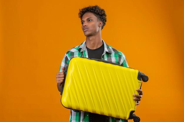 顔に真剣な自信を持って表情で脇を見てスーツケースを保持している若いアフリカ系アメリカ人旅行者