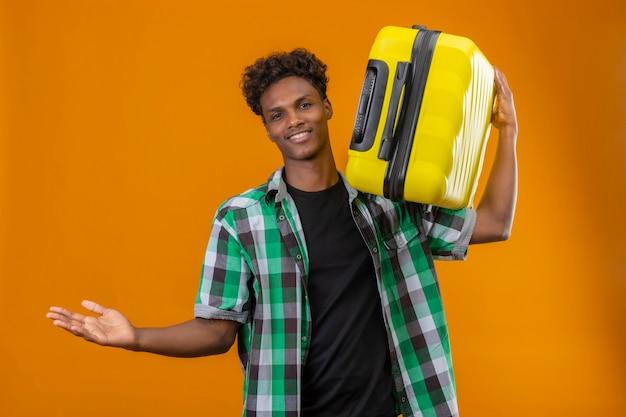 Молодой афро-американский путешественник мужчина держит чемодан, глядя в камеру, улыбаясь позитивно и счастливо разводя руки, делая приветственный жест, стоя на оранжевом фоне
