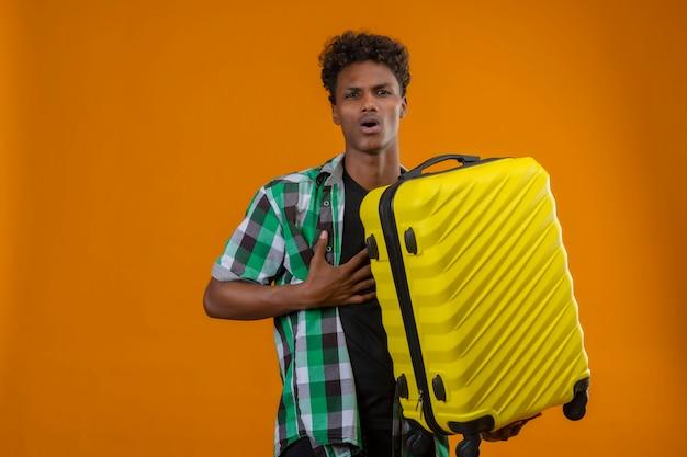 オレンジ色の背景の上に立って怖い表情でカメラを見てスーツケースを持って若いアフリカ系アメリカ人旅行者が怖い