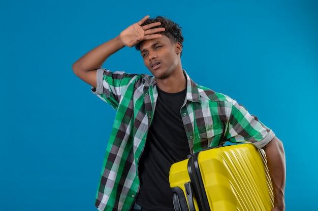 スーツケースを持って若いアフリカ系アメリカ人旅行者の男は青い背景に疲れて退屈して立っています。