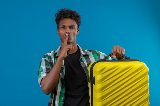 唇に指で沈黙のジェスチャーを作るスーツケースを保持している若いアフリカ系アメリカ人旅行者の男