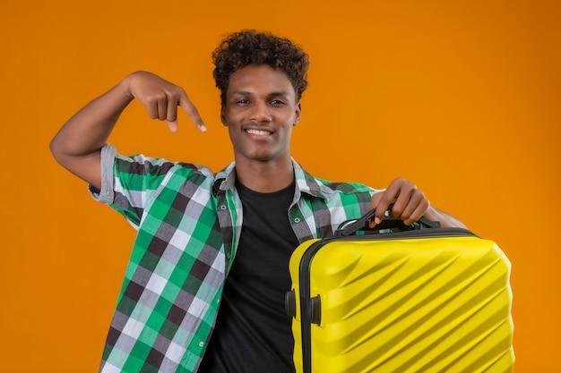 Uomo del giovane viaggiatore afroamericano che tiene la valigia che indica con il dito sorridendo allegramente