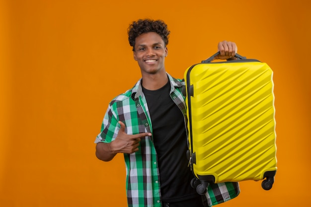 オレンジ色の背景の上に元気に立って笑顔のカメラを見てそれに指で指しているスーツケースを持って若いアフリカ系アメリカ人旅行者男