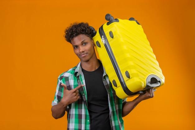 オレンジ色の背景の上に自信を持って立っている笑顔のカメラを見てそれに指で指しているスーツケースを持って若いアフリカ系アメリカ人旅行者男
