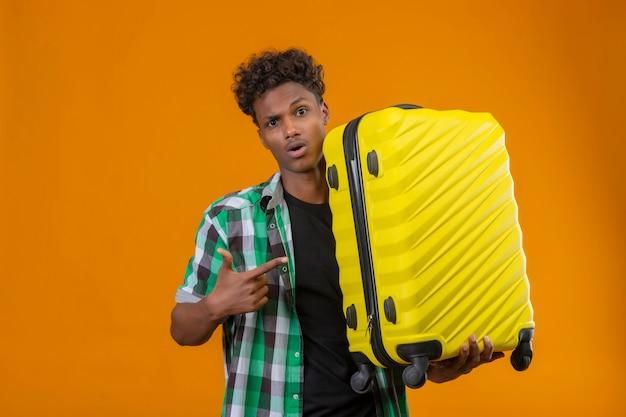 それを指で指しているスーツケースを持って若いアフリカ系アメリカ人旅行者男はオレンジ色の背景の上に立って驚いた