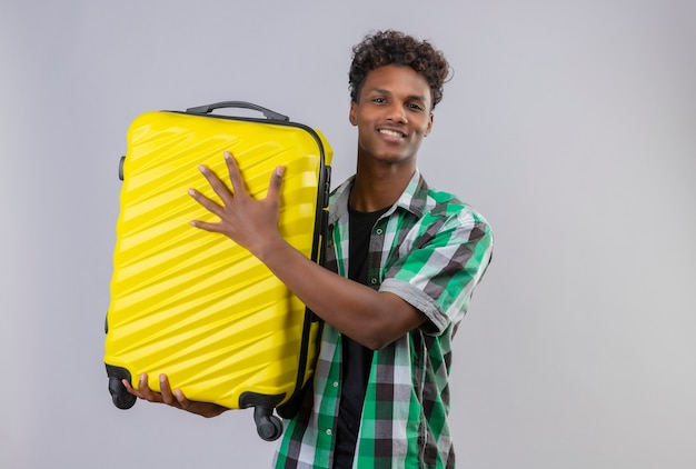 Young african american traveler man holding suitcase smiling cheerfully, positive and happy 2