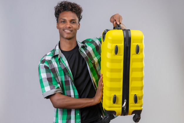 Young african american traveler man holding suitcase smiling cheerfully, positive and happy