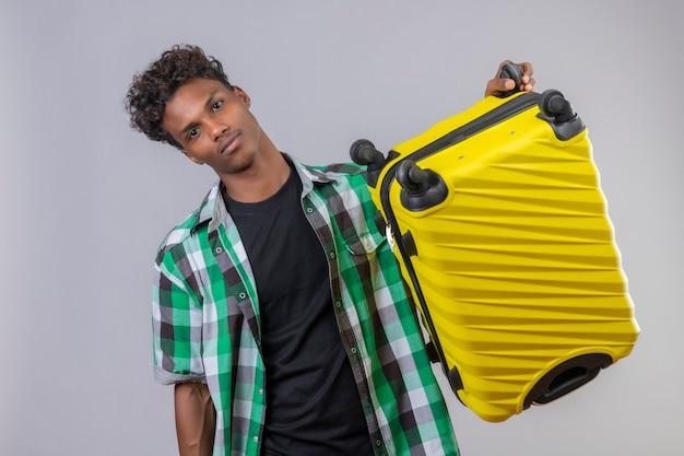 若いアフリカ系アメリカ人旅行者のスーツケースを持って疲れて、白い背景の上に立っているカメラを見て退屈