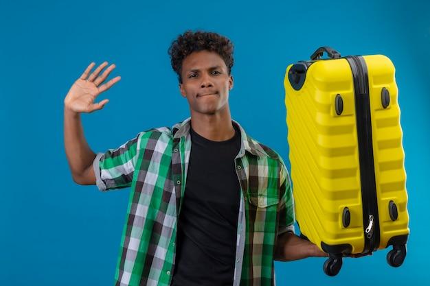 Молодой афро-американский путешественник мужчина держит чемодан, машет рукой, глядя в камеру со скептическим выражением лица, стоящим на синем фоне