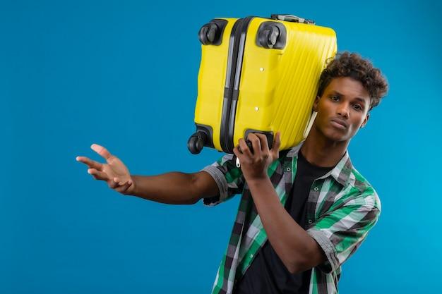 Uomo giovane viaggiatore afroamericano che tiene la valigia con espressione confusa sul viso con la mano alzata