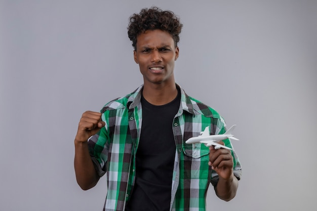拳飛行機を上げるおもちゃの飛行機を持って若いアフリカ系アメリカ人旅行者の男性が終了し、白い背景の上に立って彼の成功を喜んで幸せな拳を上げる