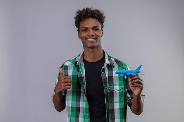 Uomo del giovane viaggiatore afroamericano che tiene aeroplano giocattolo sorridente positivo e felice che mostra i pollici in su in piedi su sfondo bianco