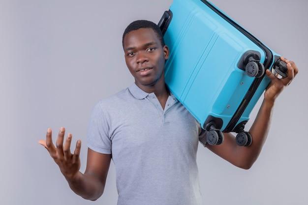 Молодой афро-американский путешественник в серой рубашке поло держит синий чемодан на плече с улыбкой на лице
