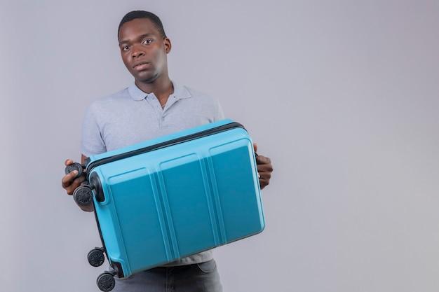 非常に心配している青いスーツケースを保持している灰色のポロシャツの若いアフリカ系アメリカ人旅行者の男