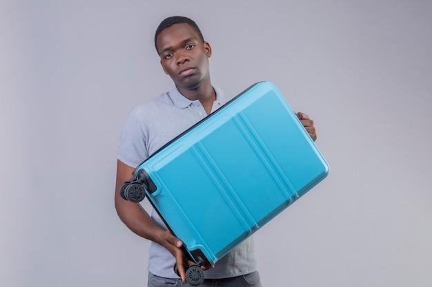 Молодой афро-американский путешественник в серой рубашке поло держит синий чемодан с несчастным лицом