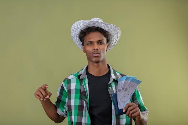 녹색 배경 위에 서 심각한 자신감 식으로 카메라를 찾고 항공 티켓을 들고 여름 모자에 젊은 아프리카 계 미국인 여행자 남자